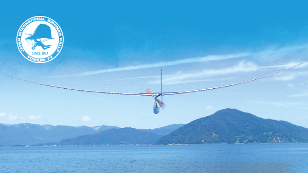 Photo of flying human-powered aircraft over Lake Biwa. Link to English version of TV program introduction of Japan International Birdman Rally in https://ytvcontents.com